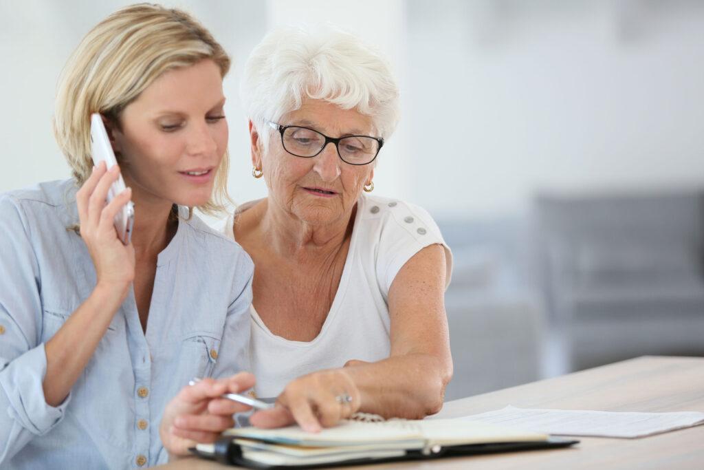 hulpdienst; oudere dame wordt geholpen om een medische afspraak te maken