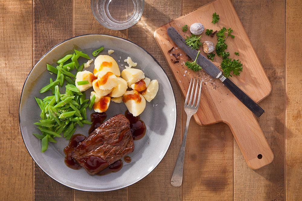 Maatlijd van tafeltje dekje, runderlapje met aardappelen en boontjes